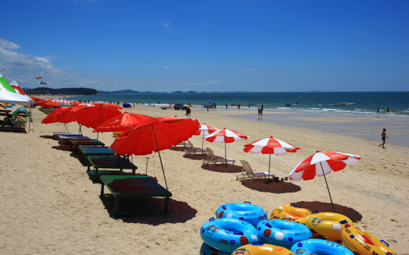 Mallipo Beach red umbrellas on sand